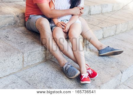 Young couple hugging and sitting on stone steps