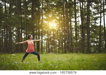 Pretty Asian woman practicing yoga in forest