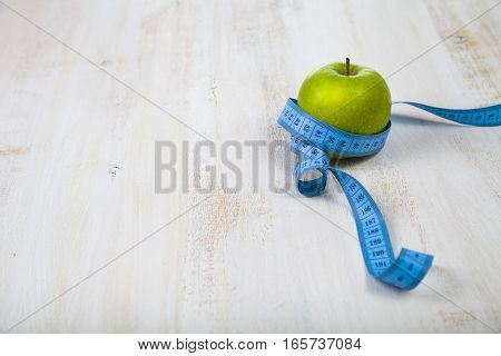 Green Apple And Measuring Tape On A Wooden Table. Concept Of Diet And Healthy Lifestyle.