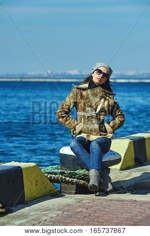 Fashionable girl in glasses on the background of the sea