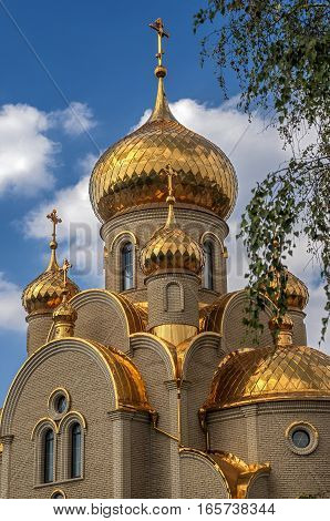 Ukraine Khartsizk . Orthodox Church of the Iberian Icon of the Mother of God . Holy spring . The gilt domes and roof . Bright sunny day blue sky with small clouds.