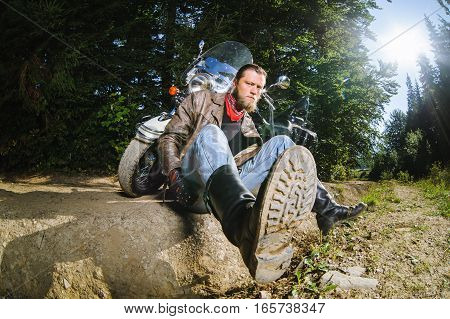 Male Biker Sitting On Dirt Road Near Motorcycle
