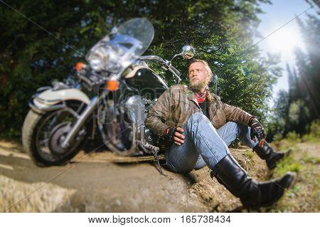 Male Biker Sitting On Dirt Road Near Motorcycle