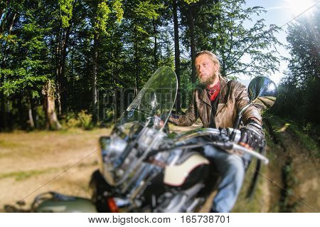 Biker Driving His Cruiser Motorcycle On Road In The Forest