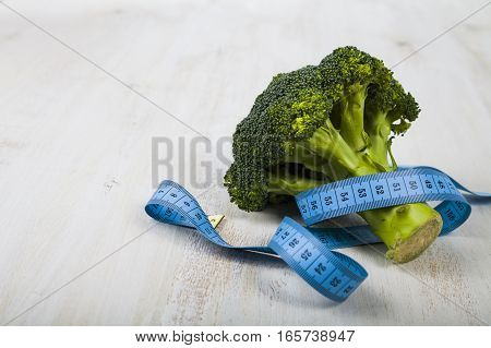 Broccoli and measuring tape on a table close-up. Concept of healthy nutrition and diet.