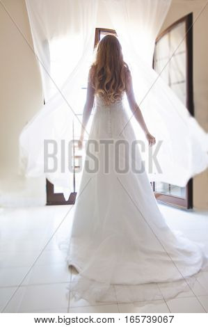 Bride in white dress standing in front of an open window