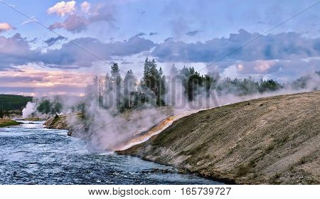 Steaming river at sunset. Hot water from the Midway Geyser Basin cascades into the Firehole River in Yellowstone National Park. Wyoming. United States.