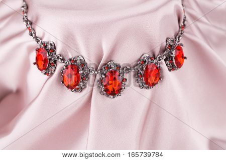 Stylish necklace with red stones on a pink fabric background.
