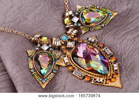 Stylish necklace with gemstones on fabric background.