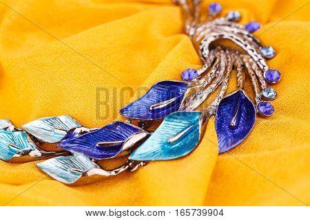 Stylish necklace on the yellow fabric background.