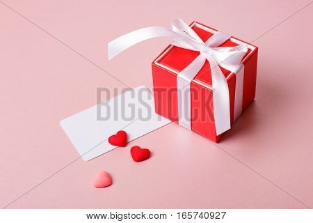 Valentine day composition: red gift box with bow credit / visiting card template and small hearts on light pink background.