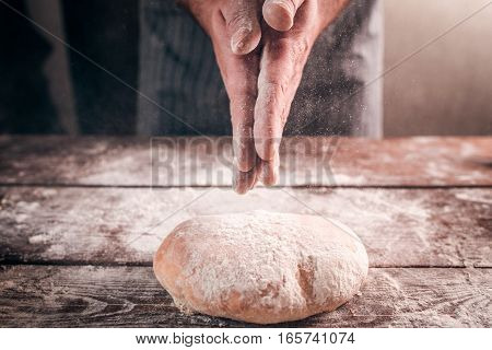 Man slap his hands above fresh bread closeup. Baker finishing his bakery, shake flour from his hands, free space for text. Homemade bakery, cooking process concept