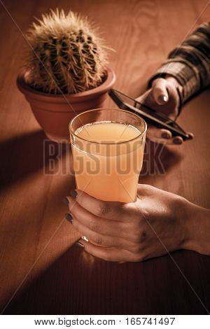 Girl Holding  Glass Of Juice And Writes  Message In The Smartphone.