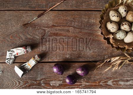 Coloring eggs for Easter holiday flat lay. Top view on wooden table with purple eggs and acrylic paint tubes, free space on wood. Handmade decoration, hobby, art concept