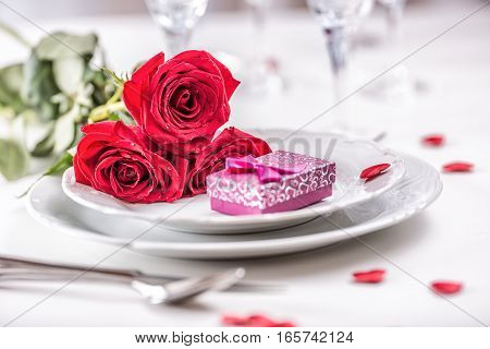 Table setting for valentines or wedding day with red roses. Romantic table setting for two with roses plates cups and cutlery.