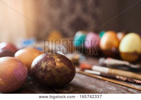 Colorful eggs with paintbrushes free space. Variety of decorated Easter attributes with art tools on table close up. Holiday, handmade, tradition , creativity concept
