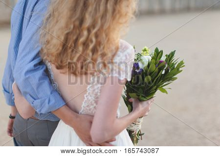 Guy hugging the girl in white wedding dress with a bouquet of flowers
