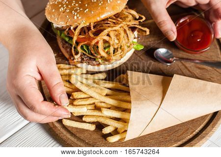 French fries eating top view. Hand taking fried potato from paper pack on tray with burger. American traditional cuisine, lunch time, fast junk food concept