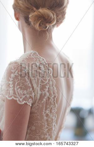 Bride in wedding dress with lace from back