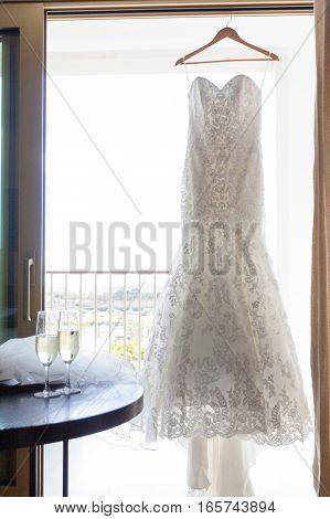 Modern white wedding dress at the window