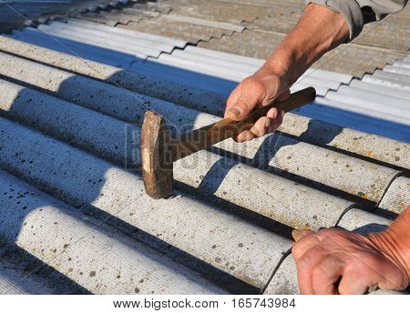 Roofer hammering nail in asbestos old roof tiles. Roofing construction poster