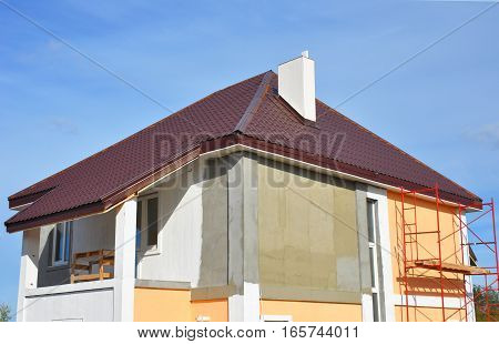 Construction or repair of the rural house with Balcony Eaves Windows Chimney Roofing Fixing Facade Insulation Plastering and Painting Walls. Painting House Facade. Roofing Construction.