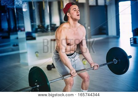Close Up Portrait Of A Muscular Male, Workout With Barbell At Training Facility, At The Gym
