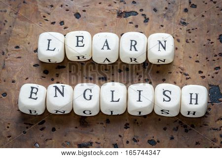 Learn english text on a wooden cubes on a brown cork background