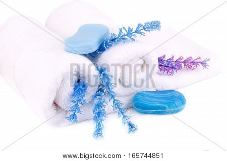 White rolled towels with soaps and flowers on white background.