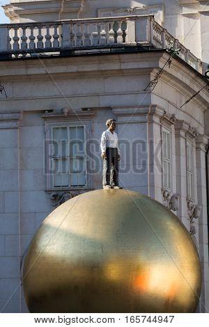 SALZBURG AUSTRIA - APRIL 29 2016: Stephan Balkenhol - Sphaera a sculpture of a man on a golden sphere on Kapitelplatz in Salzburg Austria