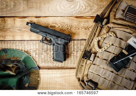 top view of the gun, backpack and a hat on a wooden table