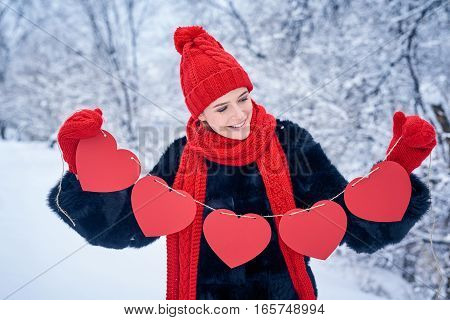 Love and valentines day concept. Smiling woman holding garland of five red paper hearts shape - blank copy space for letters or text, looking down at hearts over winter landscape