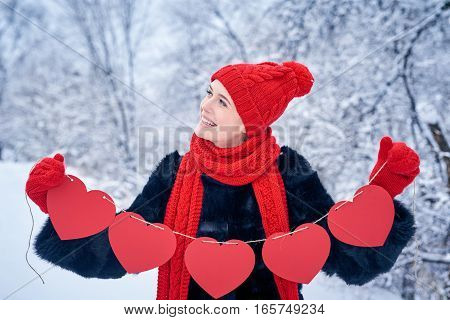 Love and valentines day concept. Smiling woman holding garland of five red paper hearts shape - blank copy space for letters or text, looking up over winter landscape