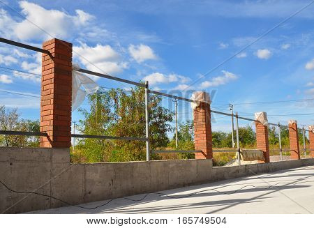 Building a Metal and Concrete Bricks Fence with Iron Bar Framework Against Blue Sky