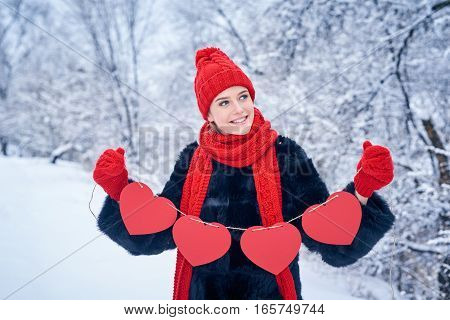 Love and valentines day concept. Smiling woman holding garland of four red paper hearts shape - blank copy space for letters or text, looking away over winter landscape