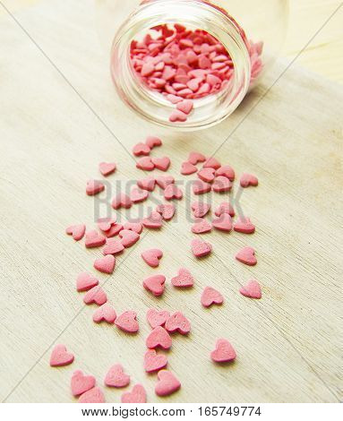 Sweet pink hearts in the jar hearts scattered on the table