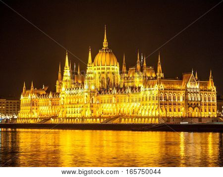 Night view of illuminated historical building of Hungarian Parliament, aka Orszaghaz, with typical symmetrical architecture and central dome on Danube River embankment in Budapest, Hungary, Europe. It is notable landmark and seat of the National Assembly