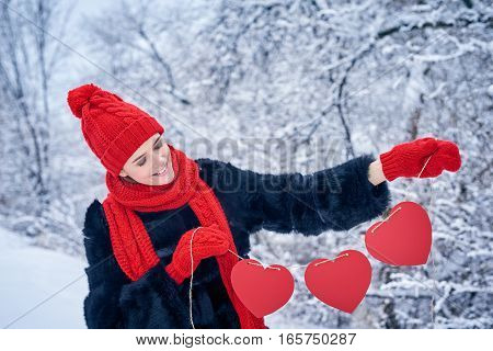 Love and valentines day concept. Smiling woman holding garland of three red paper hearts shape - blank copy space for letters or text, looking down at hearts over winter landscape