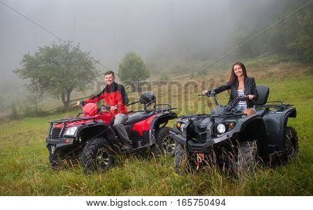 Happy Couple Driving Four-wheeler Atv Offroad