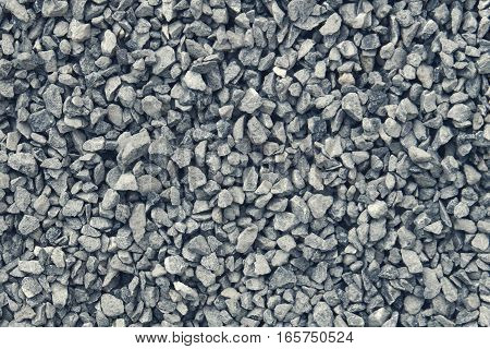 stone wall aggregate - coarse gravel / grit of glauconite sandstone with dark gray and blue cold color tone. The stones vary in shape but are mostly of similar size.