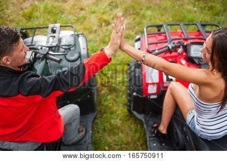 Couple Sitting On Four-wheeler Atv Giving High Five