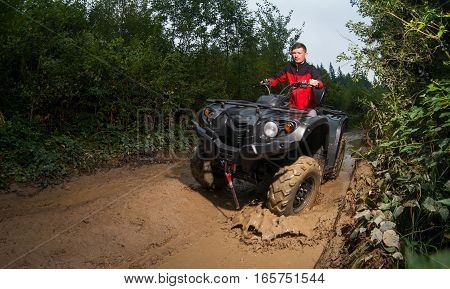 Young Man Driving Four-wheeler Atv Through Mud
