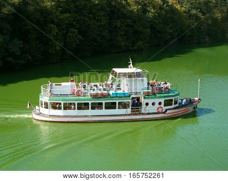 Picture of a steamboat cruising a river with blue-green algae