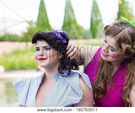 Two beautiful plus size models are sitting on the shore of the lake professional makeup and hairstyle