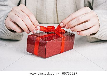 Human hands holding tips of tied red ribbon on gift box. Front closeup view