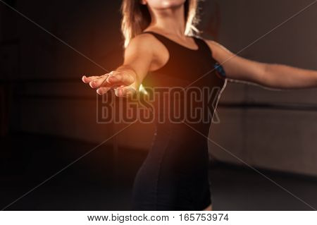 Teen dancer standing in ballet position preparing for dance routine. Girl wearing in black unitard in studio.