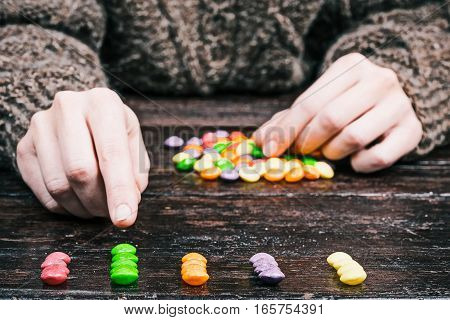 Human hands sorting colorful candy buttons by color