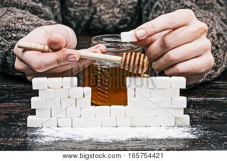 Human hands holding honey dipper and putting sugar cube to the wall on the foreground