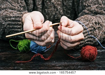 Human hands crocheting with wooden hook on the table