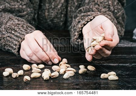 Human hands holding pistachio and scatter them to the table. Closeup front view